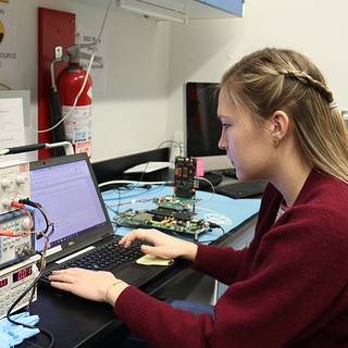 Photo of Postbaccalaureate researcher Isabella Brewer at a computer connected to electronics hardware