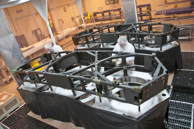 Technicians complete the primary mirror backplane support structure wing assemblies.