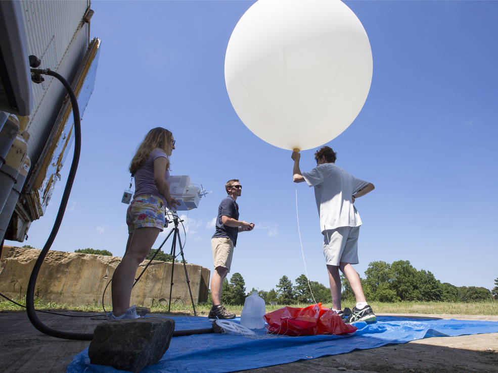 Photo of NASA Goddard post-doctoral fellow John Sullivan, center, along with interns Lindsay Rodeo, left, and Lance Nino, preparing to launch a balloon that will take ozone measurements in the skies over southeastern Virginia.