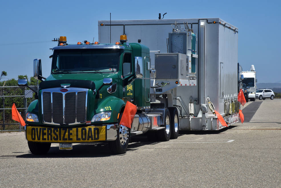 Photo of a truck carrying the ICESat-2 satellite, packed safely in a specialized shipping carrier, arriving at Vandenberg Air Force Base