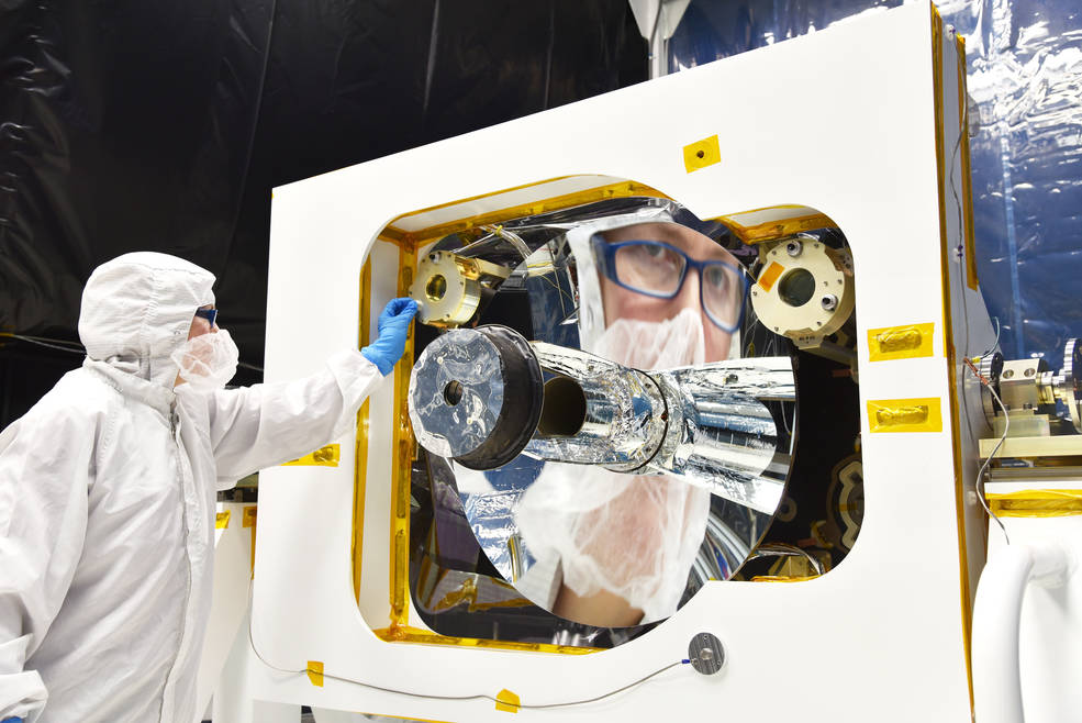 Optical Alignment Lead Engineer Bente Eegholm's reflection can be seen in the primary mirror of GEDI's receiver telescope while in the cleanroom