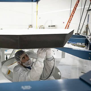 Engineer in clean room garb attaches something to the Parker Solar Probe