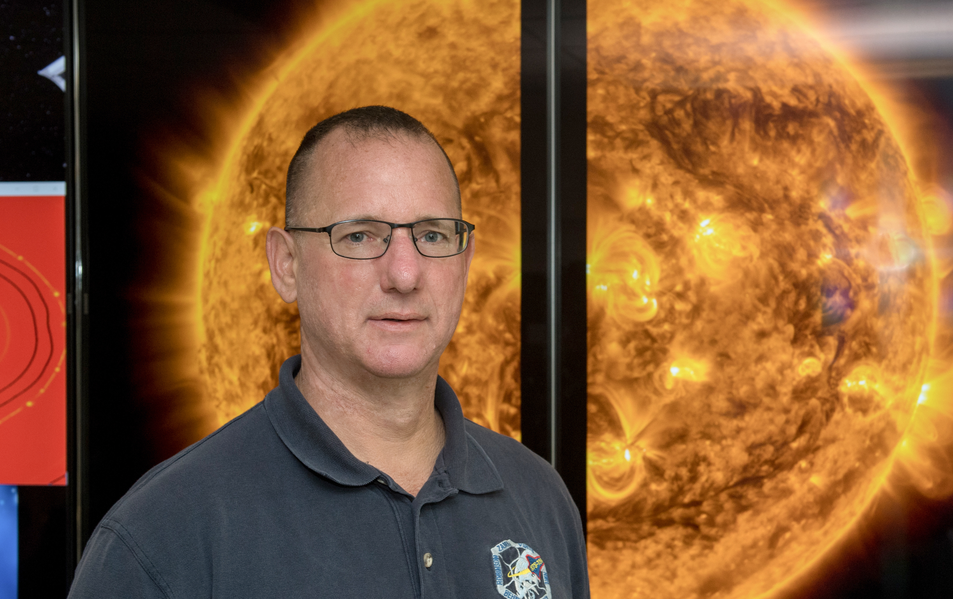 Photo of Peter Schuck in front of an image of the sun