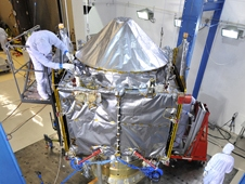 Shiny spacecraft tended to by technicians in paper suits in a clean room.