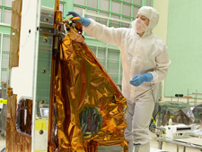 Photo of Aleksandra Bogunovic reaches across the instrument to affix the corners of a Multi-Layer Insulation blanket to the TIRS instrument.