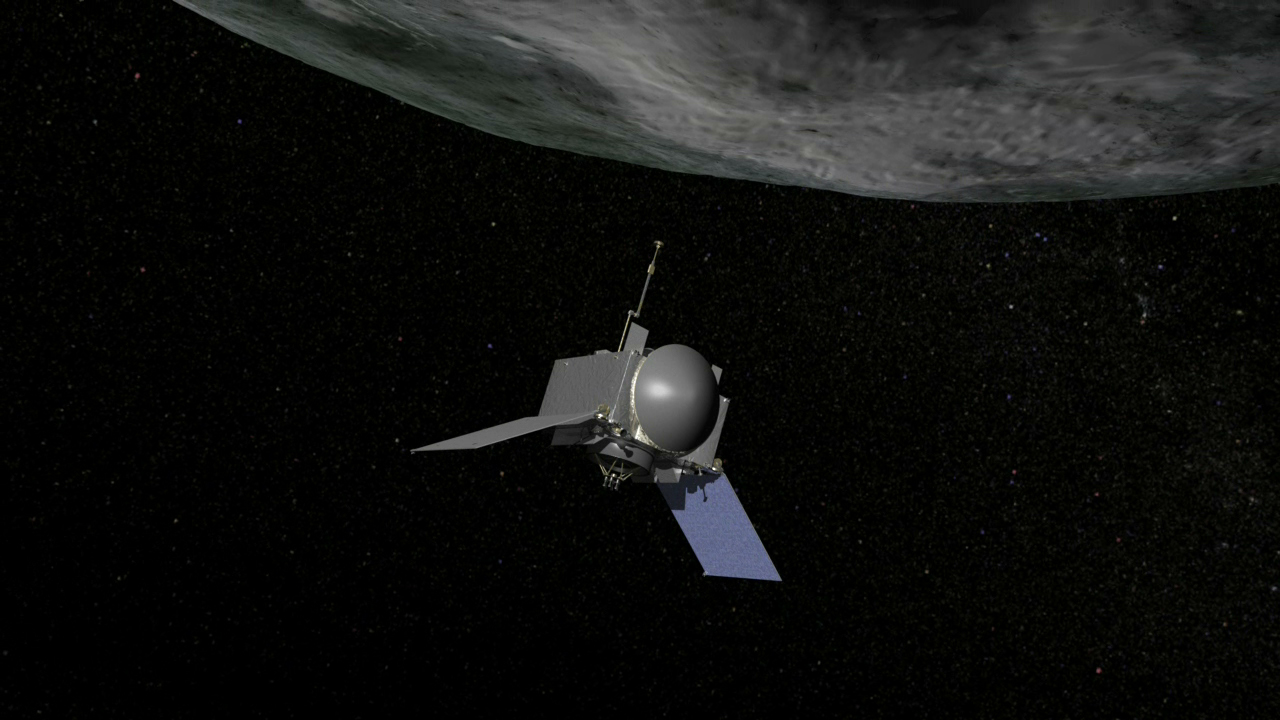 Photo of This is an artist's concept of NASA's OSIRIS-REx spacecraft preparing to take a sample from asteroid Bennu.