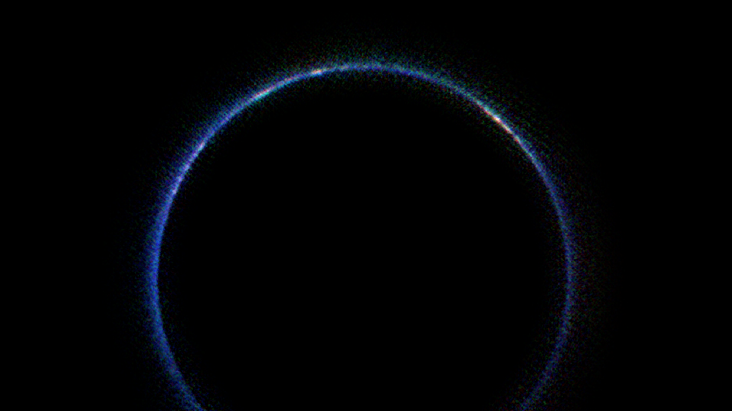 An image showing Pluto's atmosphere as a thin blue ring around the planet
