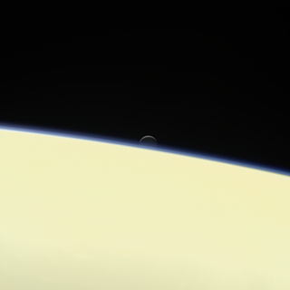 photo of moon of Saturn over the limb of Saturn