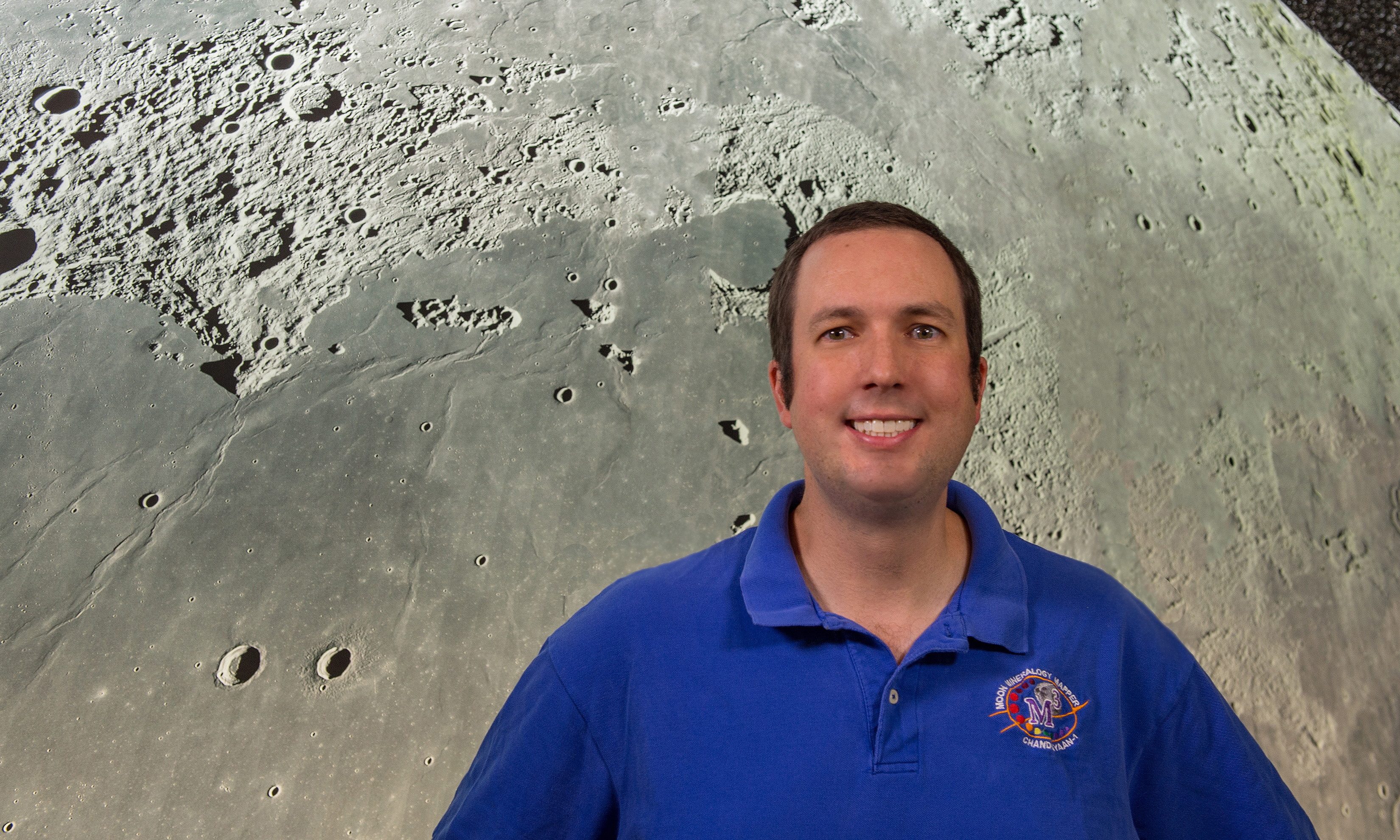 Photo of Noah Petro in front of a large photo of the Moon