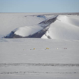Photograph of small yellow tents in a vast snowfield with mountains in the background