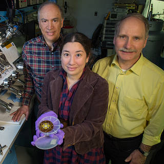 Photo of John Hagopian, Lucy Lim, and Larry Hess in a lab. Lucy is holding a small electronic device.