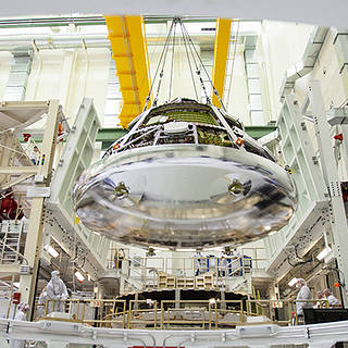 photo of the Orion crew module for Artemis 1 being lifted by a crane